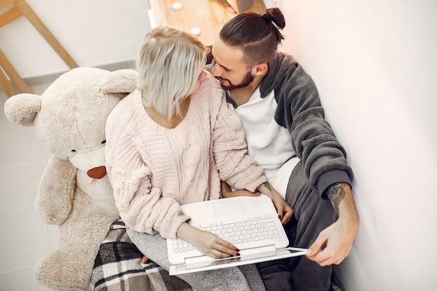 Paar zittend op een bed in een kamer en gebruik een laptop