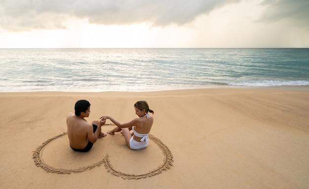 Paar zittend op het strand bij het tekenen van hartvorm op zand. tijdens zonsondergang in de zomer.