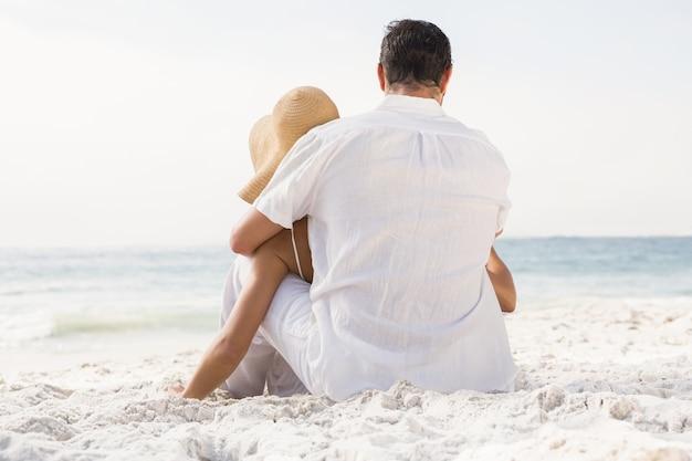 Paar zittend op zand op het strand