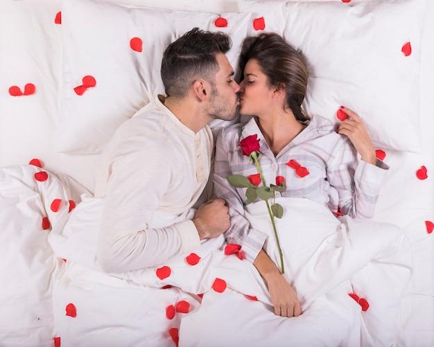 Paar zoenen in bed met rode rozenblaadjes