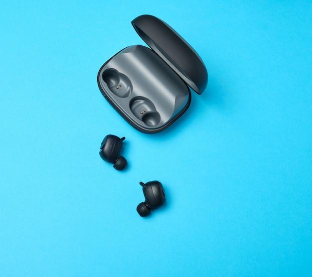 Paar zwarte draadloze kleine hoofdtelefoons en een oplaaddoos