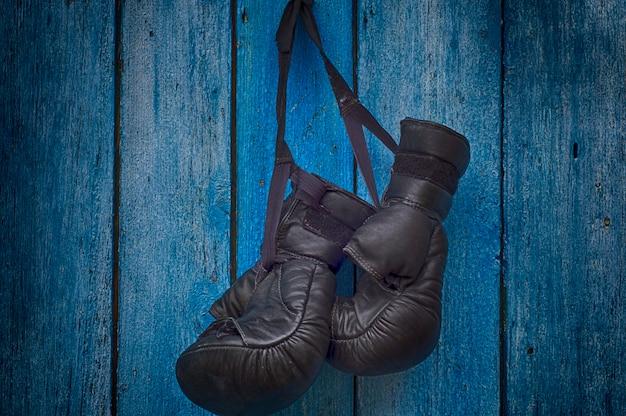 Paar zwarte handschoenen voor het thaise in dozen doen die op een spijker hangen