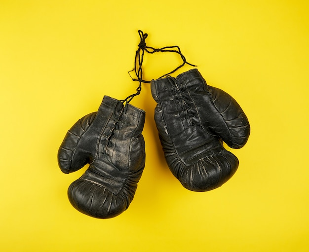 Paar zwarte leer zeer oude bokshandschoenen op een gele achtergrond