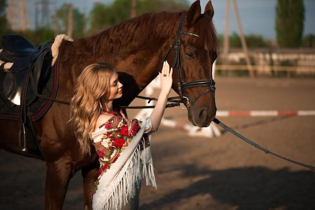 Paard en vrouw in een sjaal op de boerderij