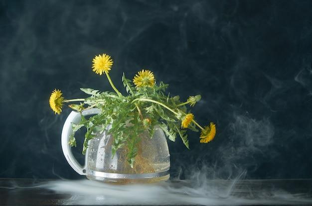 Paardebloem met wortels en bladeren in een glazen theepot