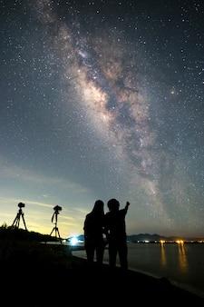Paarfotograaf die zich dichtbij de camera bevinden en melkachtige manier en sterren op de hemel kijken