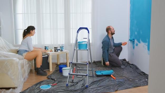 Paargesprek en huisvernieuwing. rolborstel gedoopt in blauwe verf. appartement herinrichting en woningbouw tijdens renovatie en verbetering. reparatie en decoreren.