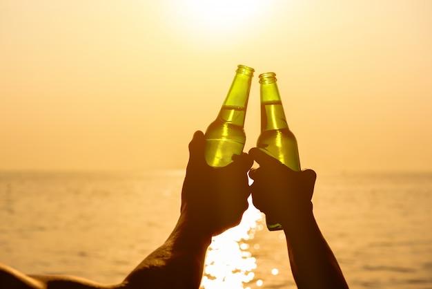 Paarhanden die bierflessen houden, die bij het strand in de zomerzonsondergang kliepen