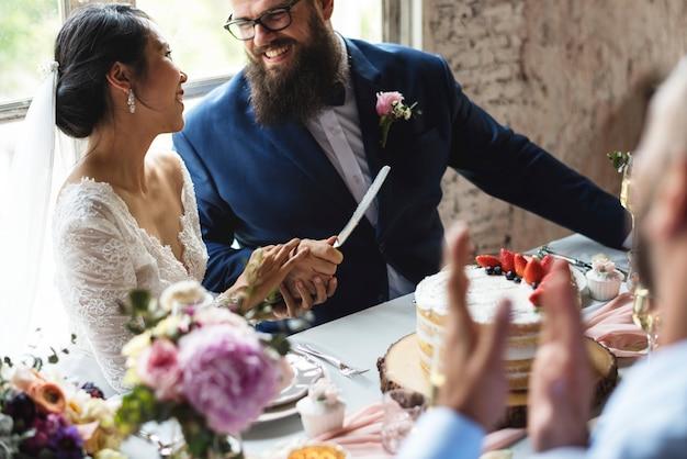 Paarhanden die het mes van de bruidstaart houden