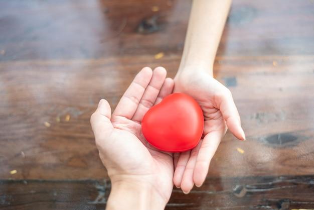 Paarhanden die rood hart houden