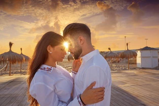 Paarjong in liefdeomhelzing op het strand