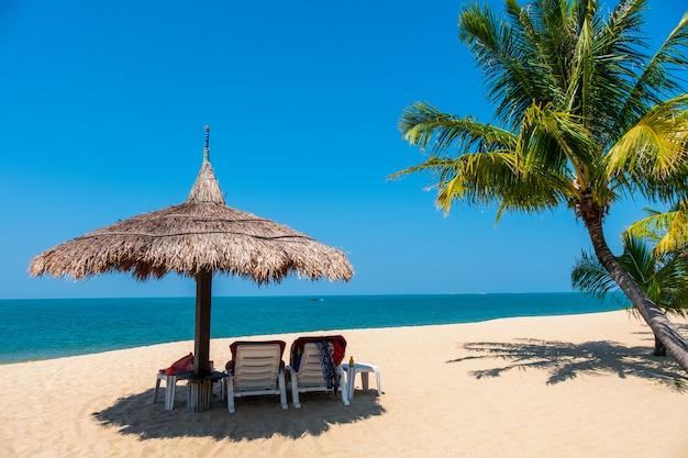 Paarligstoelen en kokosnotenpalm op tropisch strand met overzees en blauwe hemel