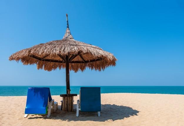 Paarligstoelen en paraplu op tropisch strand met overzees en blauwe hemel