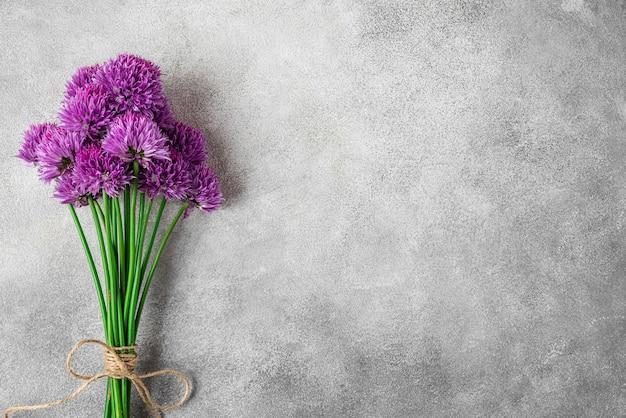 Paars alium bloemenboeket op grijze betonnen ondergrond