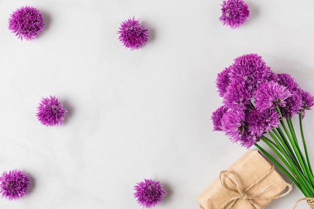 Paars alium bloemenboeket op wit oppervlak met geschenkdoos