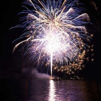 Paars kleurrijk vuurwerk op de zwarte hemelachtergrond
