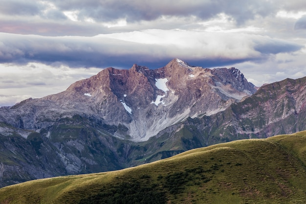 Paars licht verlicht een grote berg en de humeurige lucht