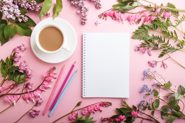 Paars lila en bloeden hart bloemen en een kopje koffie met notebook en kleurpotloden op pastel roze.