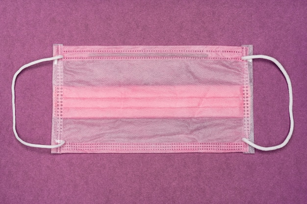 Paars medisch gezichtsmasker voor stijlvolle vrouwelijke arts op trendy violette kleurachtergrond. modieus ademhalingsverband voor verpleegster, vrouwen die neus en mond bedekken. concept lifestyle medicijnkleding