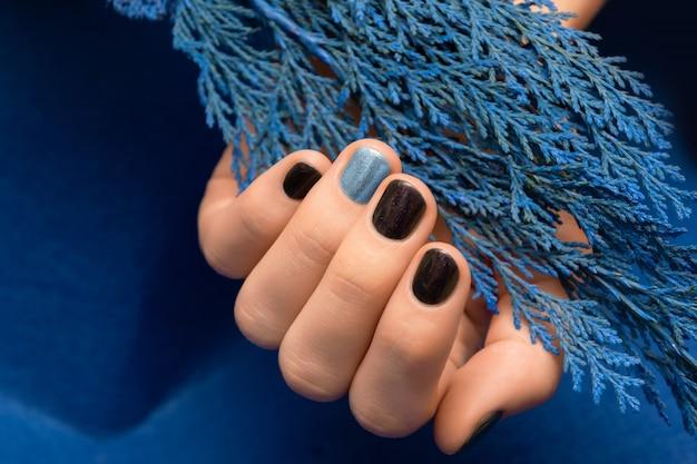Paars nageldesign met blauw accent. gemanicuurde vrouwelijke hand.