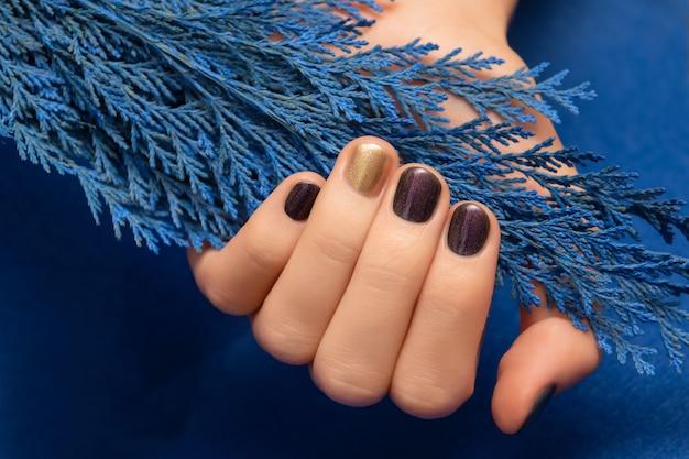 Paars nageldesign met gouden accent. gemanicuurde vrouwelijke hand.