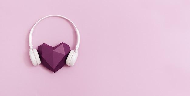 Paars papier hart in witte koptelefoon.