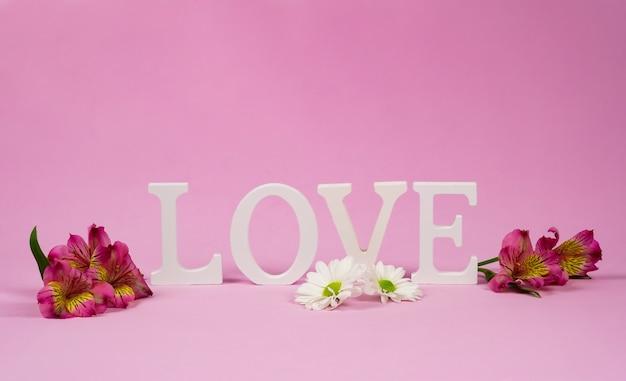 Paarse alstroemeria's en het woord liefde in de muur. kopieer ruimte voor uw tekst, roze muur