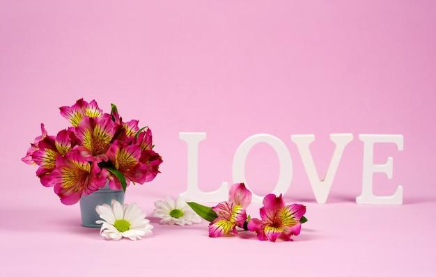 Paarse alstroemeria's op de voorgrond en het woord liefde in de muur. kopieer ruimte voor uw tekst, roze muur