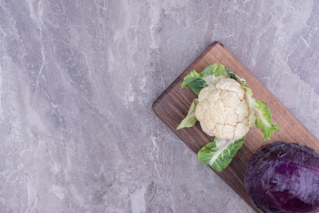 Paarse aubergine en bloemkool op marmer.
