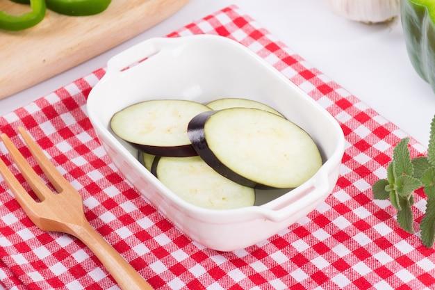 Paarse aubergineplakken in witte kom