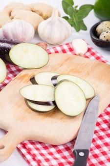 Paarse aubergineplakken op snijplank