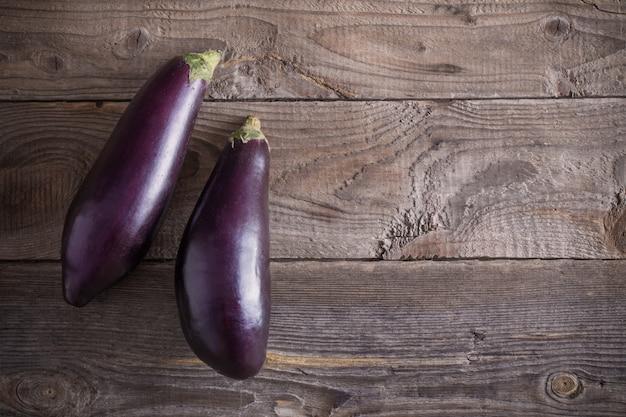 Paarse aubergines op houten achtergrond