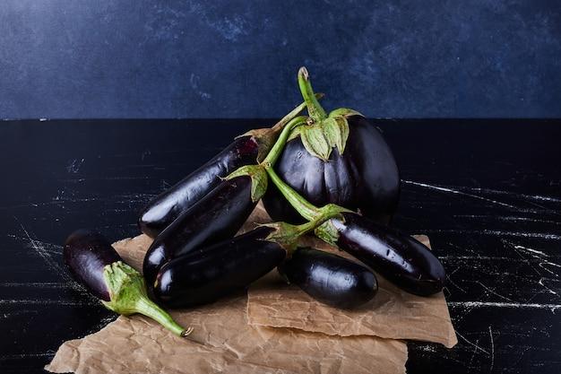 Paarse aubergines op zwart
