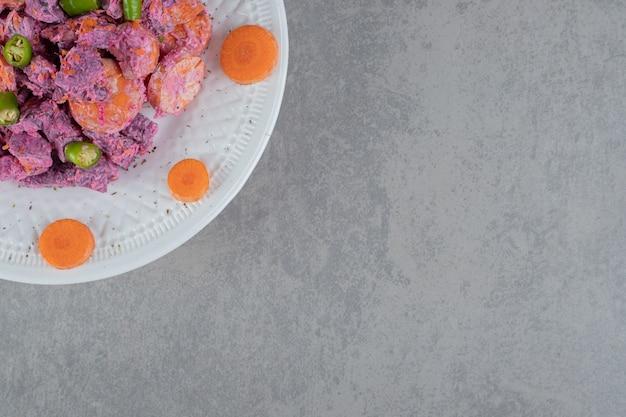 Paarse bietensalade met wortelschijfjes en zure room in een wit bord
