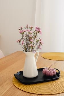 Paarse bloemboeket in een witte kruik op de houten tafel.