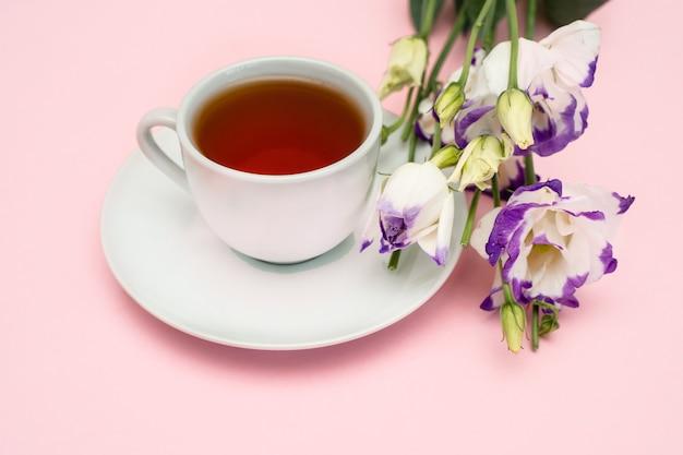 Paarse bloemen en een witte koffiekopje op een roze achtergrond. een mooie banner met ruimte om te kopiëren.