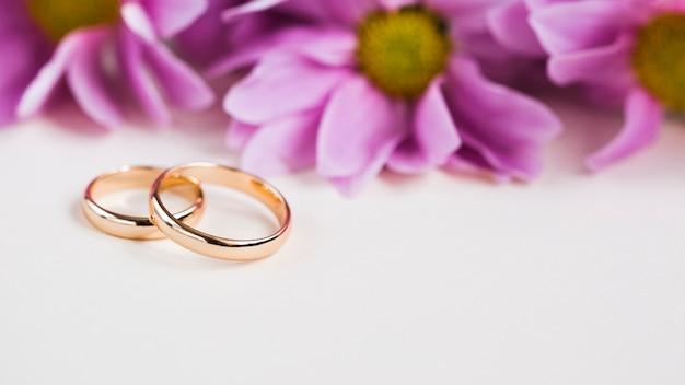 Paarse bloemen naast verlovingsringen