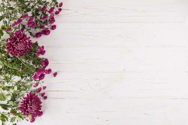 Paarse bloemen verspreid over houten tafel