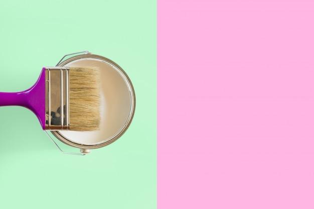 Paarse borstel met open blikje witte verf op neomunt en roze achtergrond. trend concept.