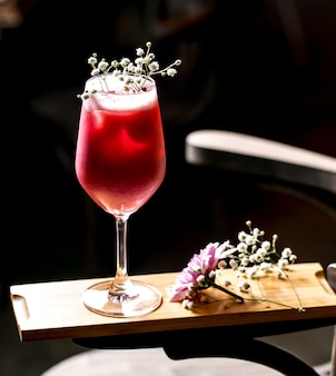 Paarse cocktail gegarneerd met gipskruid in lange standaard glas