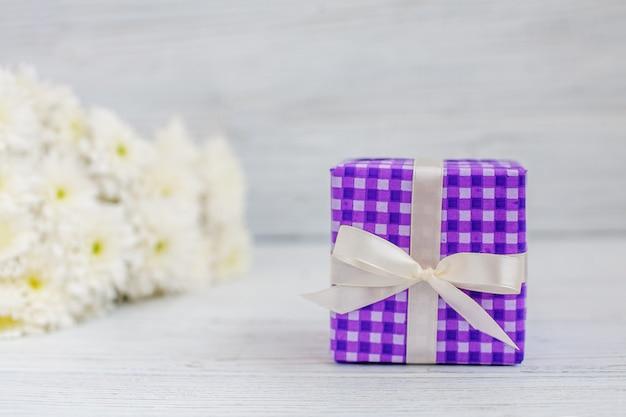 Paarse doos met een geschenk en bloemen. het concept van moederdag, verjaardag, 8 maart.