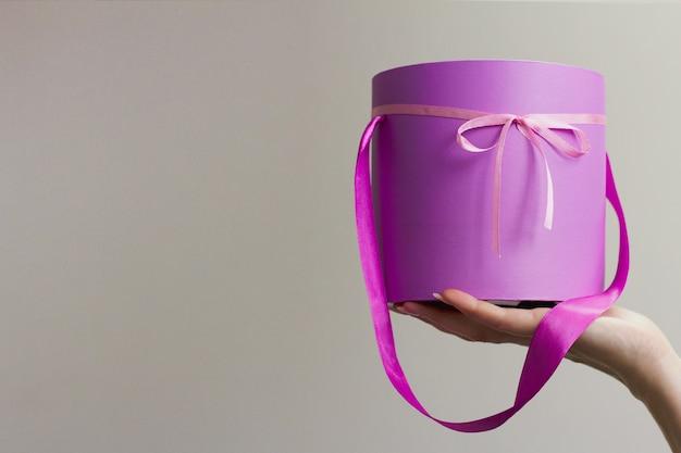 Paarse doos met roze strik in de hand van de vrouw