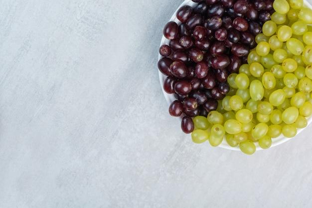 Paarse en groene druiven op witte plaat
