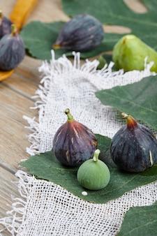 Paarse en groene vijgen op houten tafel met een wit tafelkleed en een blad, een houten lepel.