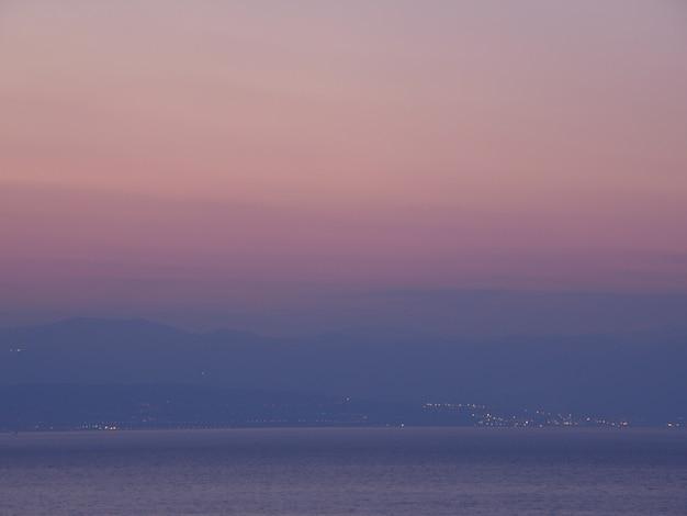 Paarse en roze kleurengradatie van zonsonderganghemel over de bergketen en de adriatische zee, opatija, kroatië