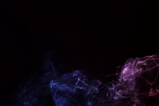 Paarse en roze rookfragmenten op een zwarte achtergrond