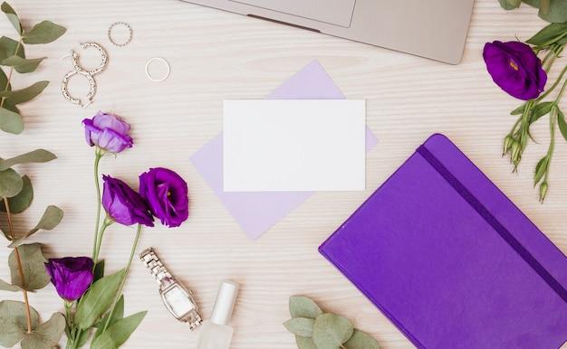 Paarse eustomabloemen; oorbellen; ringen; dagboek; polshorloge en nagellak op houten bureau