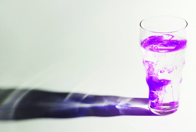 Paarse inkt lossen op in een glas water met schaduw op witte achtergrond