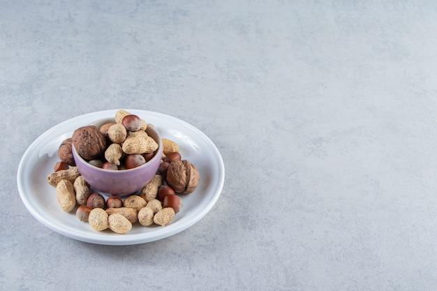 Paarse kom vol met verschillende gepelde noten op stenen achtergrond.