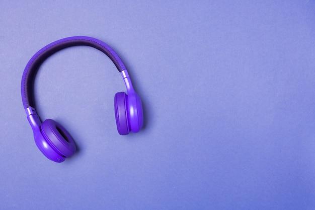 Paarse koptelefoon op paarse achtergrond, bovenaanzicht. kopieer ruimte. ruimte voor tekst.